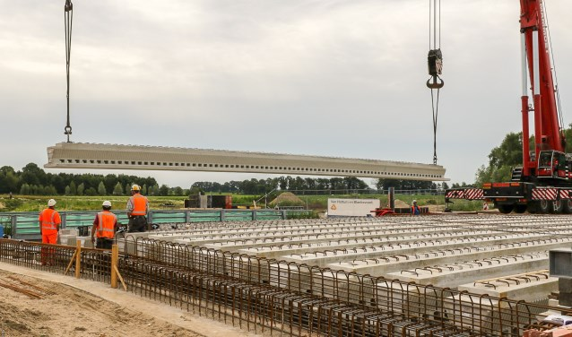 De liggers van de eerste brug zijn over de Slinge geplaatst. Daarmee bereikt deze brug bij Groenlo als eerste speciale bouwwerk van de Nieuwe Twenteroute zijn 'hoogste punt'.