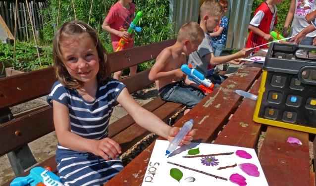 Sara lijmt nog even wat blaadjes vast en dan is het natuurschilderijtje klaar. Foto: Marianne van der Ham