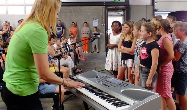 Basisschoolleerlingen zingen onder leiding van Juf Leonie en begeleid door harmonie Sint Caecilia.