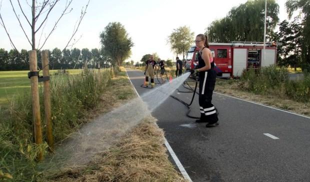 Stephan Jansen (Arkelse Brandweer) en Nikki Morelissen (Jeugd brandweer Arkel) in actie op de Vlietskade. Foto: Brandweer Arkel