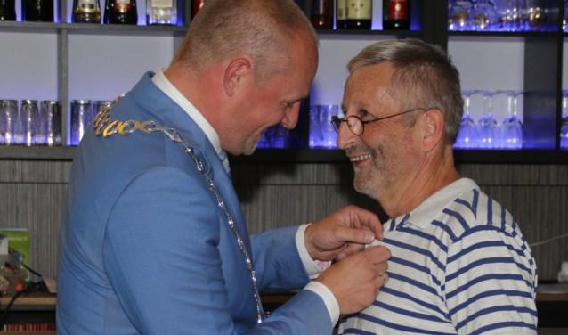 Locoburgemeester Dennis Gudden speldde het erezilver op bij Bert van de Weerd. Foto: Willem Groeneveld