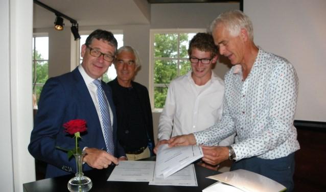 Hendrik Muilwijk miste de diploma-uitreiking, maar kreeg toch nog zijn papiertje. Wethouder Kees van Velzen (li) reikte het diploma uit, met support van Michiel Gerritsen en Peet Stolwijk (re).