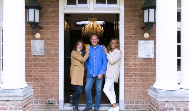 Meindert van Buuren tussen mede-organisatoren Karen Kreukniet (links) en Barbara van Buuren in de deuropening van het landhuis op Landgoed Olaertsduyn.