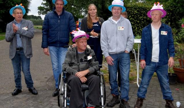 Vijf jubilarissen die al twintig jaar als hulpboer werken op de zorgboerderij: Raymond, William, Albert, Rob en Yuri. In het midden staat dochter en begeleidster Renee van de Groes.