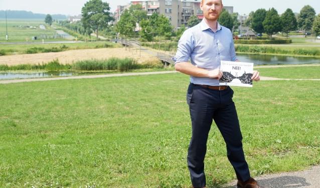 Elias Bom met in zijn handen de poster die vier maanden geleden werd verspreid en die nog altijd te zien is achter een kwart van de ramen in Molenvliet
