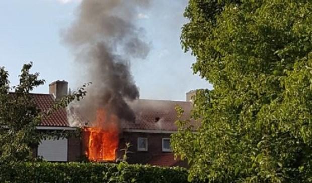 De vlammen slaan uit de slaapkamer van de rijtjeswoning. Foto: Margriet Cats-Kwant
