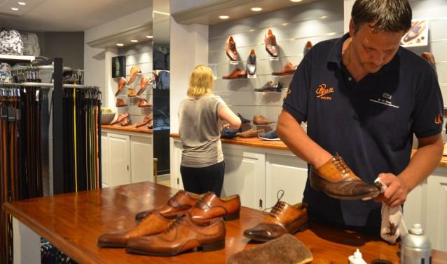 Mark is een paar schoenen aan het shinen, terwijl Annemieke de schoenen voor de presentatie op de plek zet. FOTO: Ben Blom