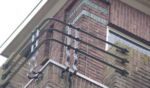 Het siersmeedijzerwerk van een balkon bovenaan een van de slanke torens valt op door geometrische vormgeving.
