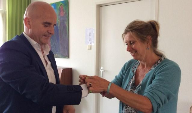 Myriam Söder bevestigt het Braziliaanse geluksbandje aan de pols van wethouder Ronald Bakker en wenst hem veel geluk toe tijdens zijn wandeltocht naar Santiago de Compostela.