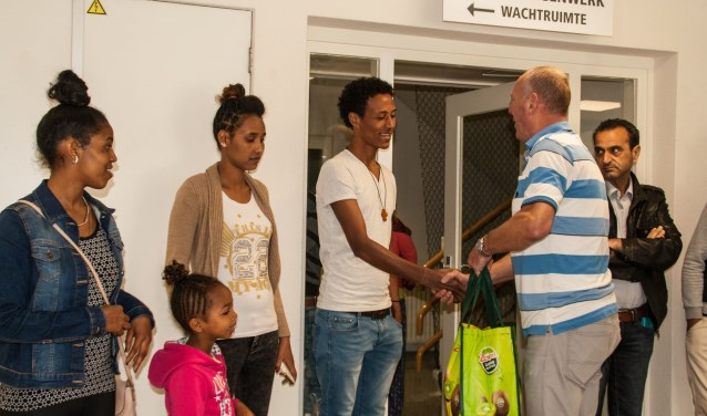 Uit handen van Peter Vermeij ontving een statushouder een  boodschappentas. Foto: Jacques Stam