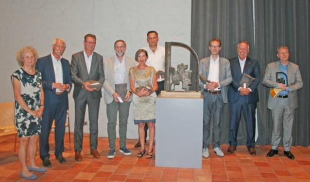 Voorzitter ton van Balken, Maria van Gerwen en de zeven hoofsponsoren van het Beeld Sint Maarten. Zij staan om een studiemodel van het uiteindelijke beeld. Foto: Robert van Dijk