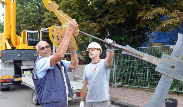 Gert Vendrig, voorzitter van de Kerkcommissie haalt de kerkhaan van het kruis van de 100 jaar oude Sint Bavokerk