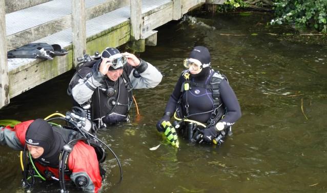 Duikers van de Alphense Duikvereniging Atlantis, Patrick van Rooij, Walther Brussee en Jacqueline Slagter, bereiden zich voor op een duik in de Zegerplas om onderwatermetingen te verrichten.