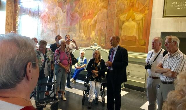 Na te zijn welkom geheten door wethouder Huib van Olden op het Bossche stadhuis geeft een lokale gids de ouderen uitleg over de geschiedenis van Den Bosch.  foto: Ria Monsieurs-Smith