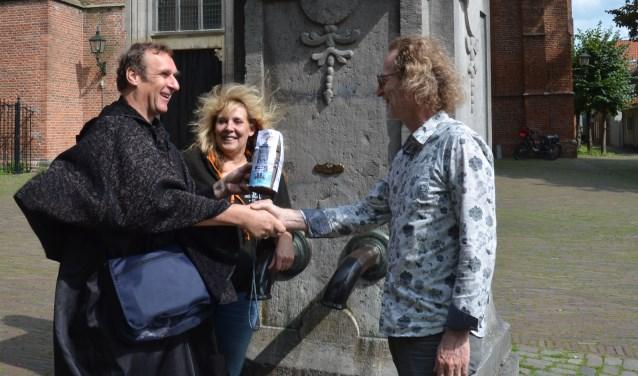 Carolien Smit, initiatiefnemer van het festival, kijkt geamuseerd toe hoe Peter de opbrengst aan Jos Soons, van stadsbrouwerij de Dikke, overhandigt. FOTO: Ben Blom