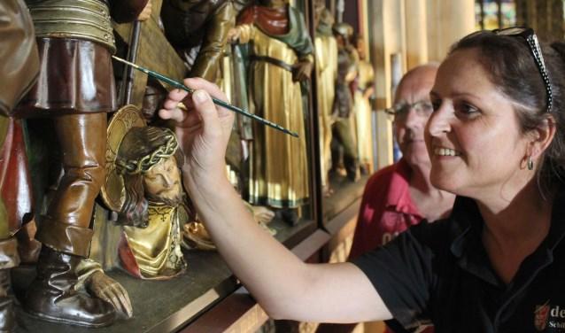 Gonny de Jongh is bijna twee jaar bezig met het restauratiewerk in de basiliek. Wil van Doorn kijkt toe bij de minutieuze restauratie van de staatsies. (Foto: Lysette Verwegen)