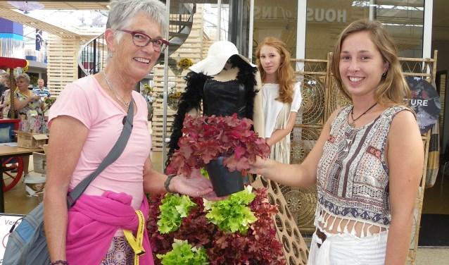 Inge van Bekkem uit Reeuwijk- Dorp (links) ontvangt een Heuchera plant van de zusjes Fleur en Kelly Kempen (rechts) bij het verlaten van de beurs. FOTO: Morvenna Goudkade