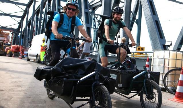 """Benno en Martijn op de tijdelijk voor auto's afgesloten IJsselbrug. """"Dit is echt een goed voorbeeld van de hindernissen die wij wel kunnen nemen en bestelbusjes niet."""" (foto: Feikje Breimer)"""