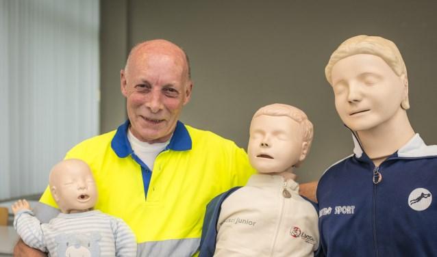 """Kaderinstructeur Wim Stuart is al meer dan vijftig jaar lid van EHBO vereniging Wijchen. """"Met deze familie van poppen leren onze leden hoe ze reanimatiehulp verlenen aan alle leeftijden."""" (foto: Jimmy Israël)"""