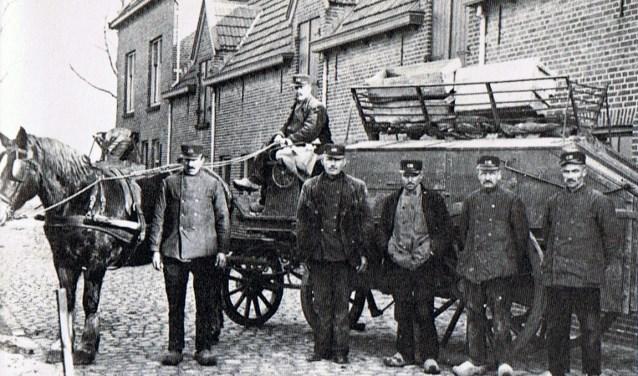 Vuilniswagen met personeel omstreeks 1930, gefotografeerd bij het voormalige gebouw van Gemeentewerken aan de Rotterdamseweg (later ToMaDo). Van links naar rechts: Paard, J. Verhoeve, A. Verbeek (op de bok), K. Hoogerland, P. Buitendijk, F. Klingeman en S. Stoop.