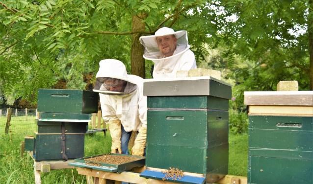 Geert Hummelen (r) en Teake de Jong aan het werk met hun bijen.