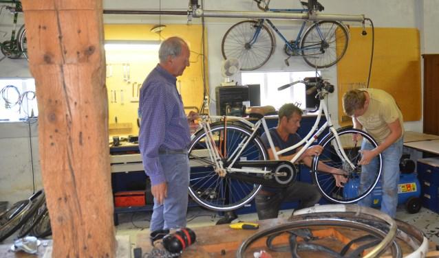 In de Deel, onder de balken worden fietsen gerepareerd door v.l.n.r. Jan Burger, begeleider Jan Maarten Dijk en Tom van der Staaij. In dezelfde ruimte worden gebruikte meubels gepimpt in samenwerking met Chris de Keijzer van Kringloop Dorestad. FOTO: Ben Blom