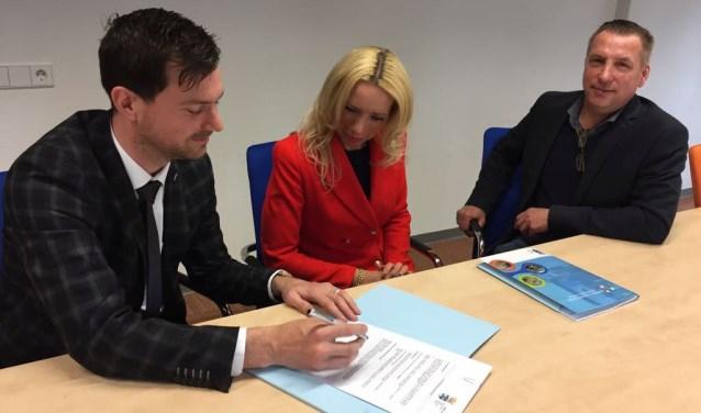 Ondertekening koopovereenkomst. Rechts de heer en mevrouw Dubbelman en links wethouder Bos.