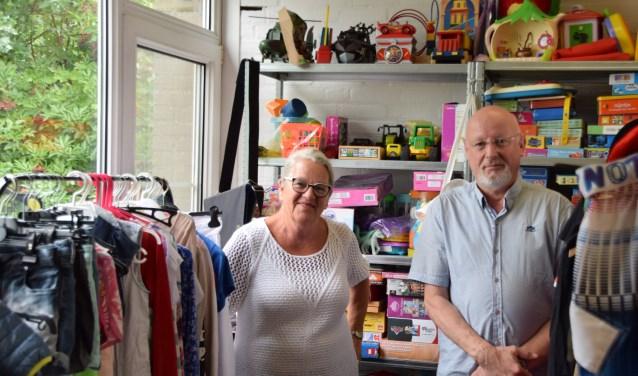 Lieda Dekker en Herman van Ooijen temidden van de vele spullen die stichting Pallium heeft ingezameld. Elke donderdag kan men tussen 9.30 tot 12.00 uur gratis kleding ophalen. (Foto: Hanneke Hoefnagel)