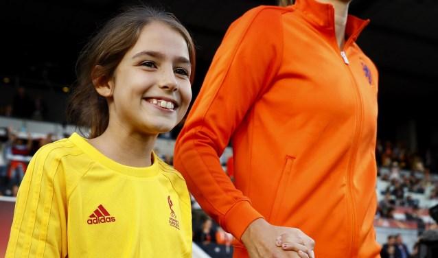 Jackie van Zijl (10) loopt met haar idool Anouk Dekker het veld op tijdens de wedstrijd Nederland-België in Tilburg.