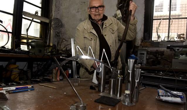 Menno Meijer in zijn werkplaats, waar hij van restafval nieuwe kunstobjecten maakt. Foto: Marianka Peters