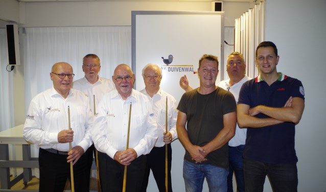 Het bestuur poseert trots in hun nieuwe outfits naast de sponsoren en kampioen Dave Christiani (geheel rechts).