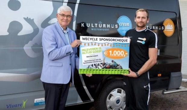 Wethouder Hans Breunissen (links) overhandigt de Wecycle-sponsorcheque voor de Speelmobiel aan Timo Riphagen, Combinatiefunctionaris Sport van Stichting Kulturhus Westervoort