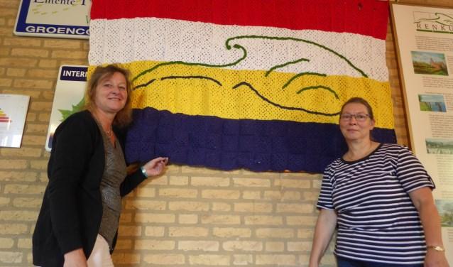 Sylvia en Marja bij de gehaakte vlag in het gemeentehuis van Renkum. (foto: Marnix ten Brinke)