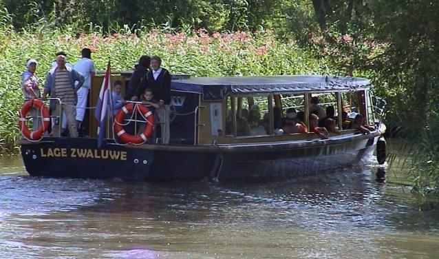 Deelnemers aan de fluistertochten varenmet een op zonne-energie aangedreven fluisterboot.