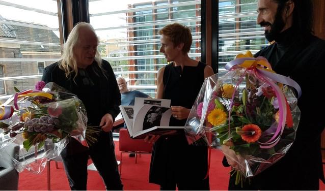 Gijs Dragt (links) en Bob Biloows overhandigen hun boek aan voormalig  directeur Zwolse theaters, Margreet Wieringa.