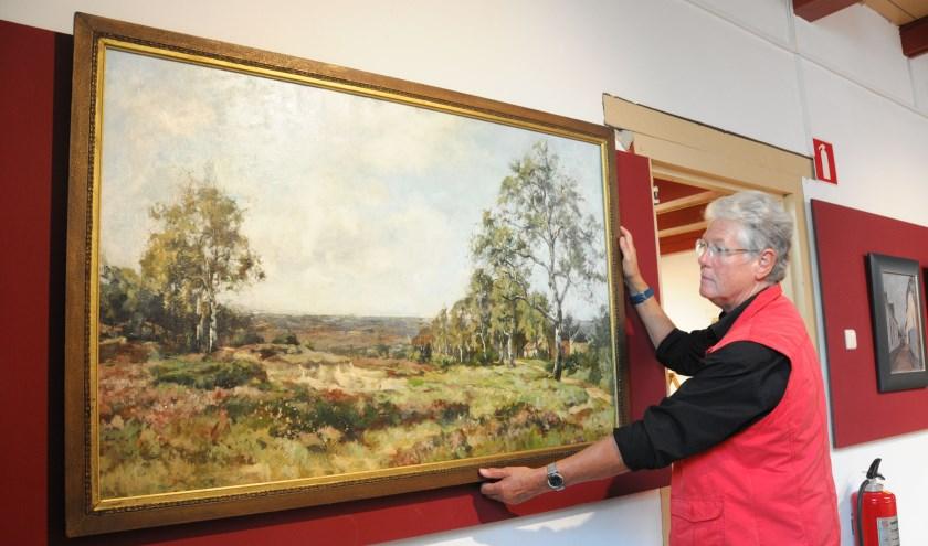 Lies van de Beek hangt het Natuurlandschap recht in het Voerman Museum Hattem, in de zaal waar ook de werken van Jo Koster zijn verzameld. (foto: Voerman Museum Hattem)