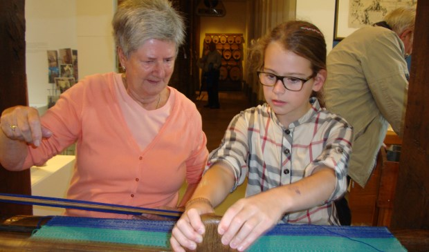 Riet Stoop leert de jeugdige Marlies van der Wiel hoe je moet weven.