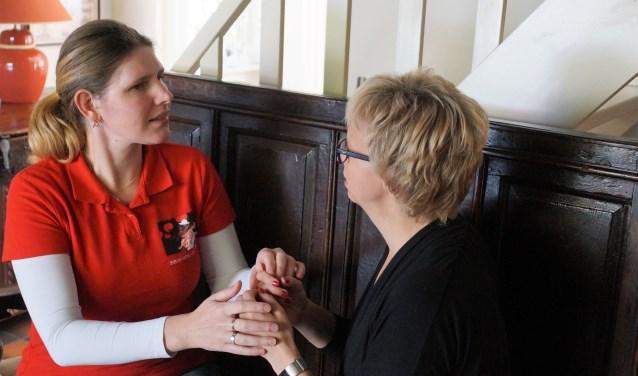 Gaby Wynia concentreert zich op wat haar tolk Lieke van Rooij haar vraagt. Voor doofblinde mensen is het handalfabet een belangrijke manier van communiceren vanwege de dubbele beperking.