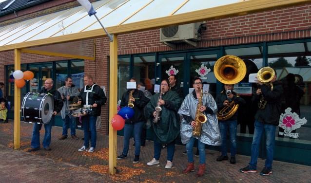 Dweilband De Koele Band lekker onder een afdak bij het winkelcentrum aan de Rijksweg. De band hield daar de stemming erin.