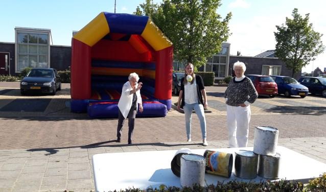 Marcella Gerritsen (midden) van EBC Zorg kijkt toe terwijl buurtbewoners zich vermaken met oer-Hollandse spelletjes.