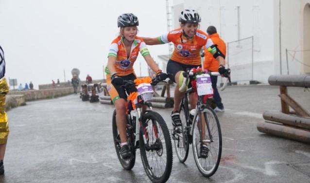 Moeder en dochter Lotte (links) en Agnes van Meer die samen aankomen op de top. Elkaar steunend om de laatste meters af te leggen. Vermoeid en voldaan, blij dat ze het gehaald hebben. Foto: Colsensation