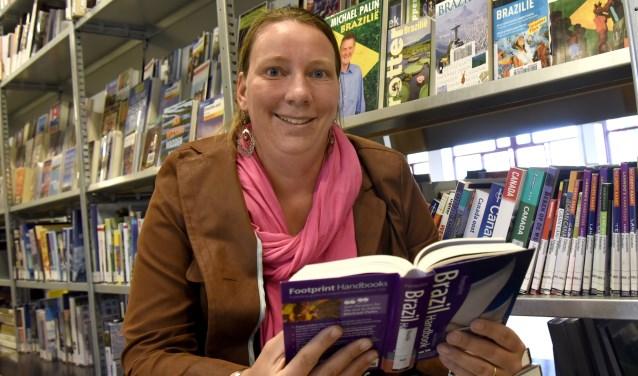 Jacoline Groenendijk bekijkt de enorme collectie Braziliëboeken in de biblioteek. De laatste keer dat ze hier was, was het nog gemeentekantoor, waar ze haar papieren voor Brazilië ophaalde. Foto: Marianka Peters
