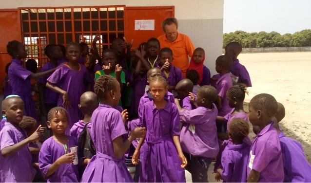 Jaap van Duuren (in het oranje) met de leerlingen bij het nieuwe gebouw van de school in Gambia.