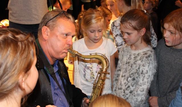 Alexander Beets geeft met zichtbaar plezier uitleg over zijn saxofoon aan de aanwezige kinderen. (Foto: Quirine van Mourik)