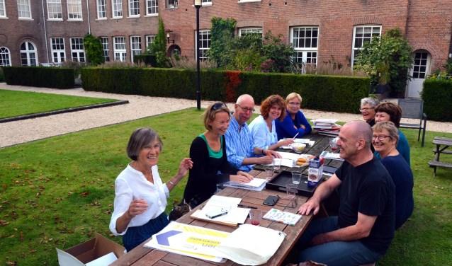 De bewonerscommissie in vergadering bijeen. En wie over zo'n mooie binnentuin doet dat op een zonnige dag uiteraard buiten. (Foto: Jos van Leeuwen)