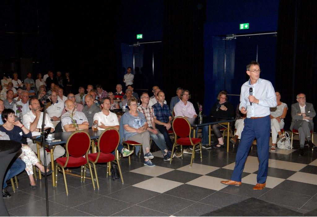 Hans van der Werff van bureau Berenschot het conceptrapport toe aan de zaal. (Foto: Tom Oosthout)