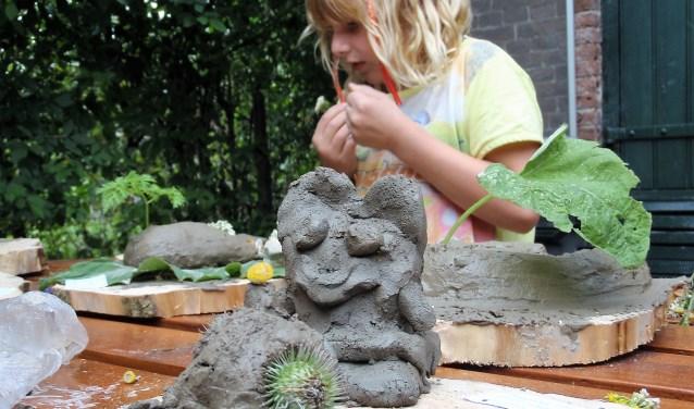 Een 'jonge kunstenaar' aan het werk. Voor de kunstroute zoekt Het Dijkmagazijn woensdag 13 september jonge kunstenaars die met de stenen die langs de Waal liggen keienkunst maken.