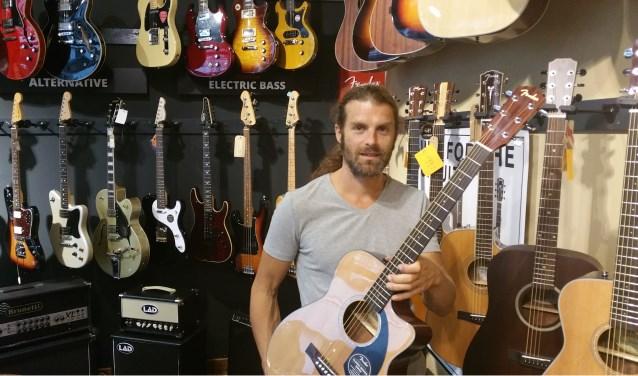 Jasper Schutten met gitaar in zijn winkel aan de Meddosestraat. 'De baard is tijdelijk. Ik ben in oktober figurant bij de Slag om Grolle'.