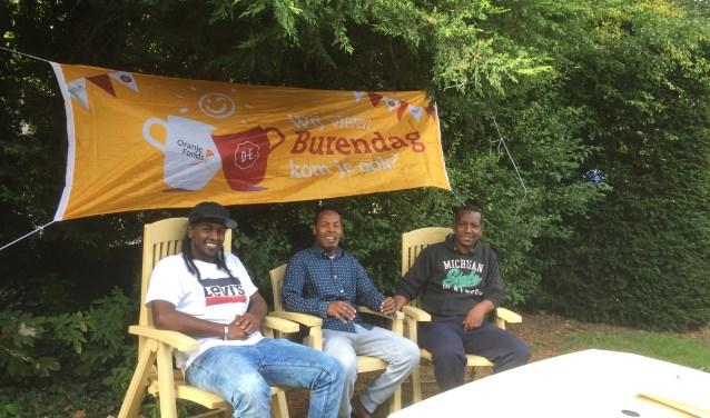 Foto. Drie van de heren poseerden onder het burendagspandoek in de achtertuin. V.l.n.r. Samson, Abdulkadir en Simon.