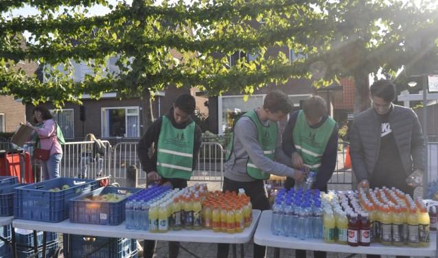 Vrijwillgers die bij de eindpost het drinken en eten klaarzetten voor de renners.